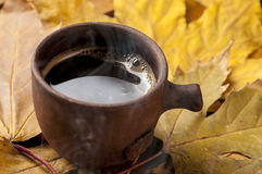 Filiżanka i jesień liście na drewnianym stole Zdjęcia Stock