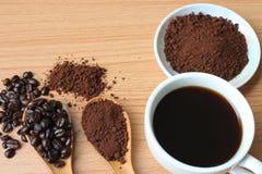Filiżanka i kawowe fasole na drewno stole zdjęcia royalty free