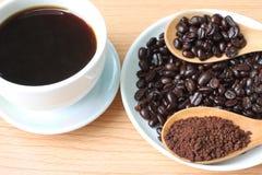 Filiżanka i kawowe fasole na drewno stole zdjęcie royalty free