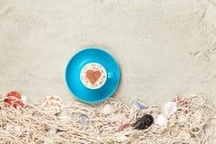 Filiżanka i sieć z skorupami na piasku Fotografia Stock