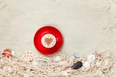 Filiżanka i sieć z skorupami na piasku Zdjęcie Royalty Free