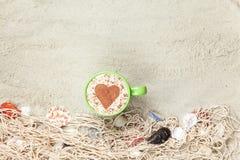 Filiżanka i sieć z skorupami na piasku Zdjęcie Stock