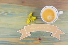 Filiżanka i stokrotka kwitniemy z życzenie kartonowym sztandarem na drewnianym stole Ładnego dnia romantycznego pojęcie Obraz Royalty Free