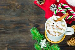 Filiżanka kakao z marshmallows, lizakami, jodłą, sosnowymi rożkami, choinki gałąź i płatek śniegu na drewnianym tle, zdjęcie stock