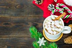 Filiżanka kakao z marshmallows, lizakami, jodłą, sosnowymi rożkami, choinki gałąź i płatek śniegu na drewnianym tle, zdjęcia stock