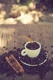 Filiżanka, kawowa fasola na drewnianym stole i Kawowa roślina vi Obrazy Stock