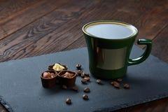 Filiżanka, kawowe fasole, czekoladowi cukierki na kamieniu wsiada nad drewnianym tłem, selekcyjna ostrość, zakończenie Obraz Stock