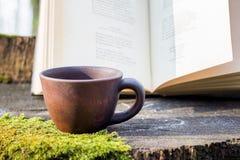 Filiżanka kawy blisko rezerwuje na fiszorku w lasowych Czytelniczych książkach i fotografia royalty free