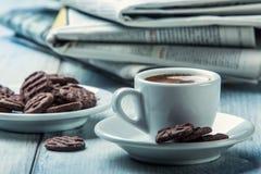 Filiżanka kawy, czekoladowi ciastka i tło gazeta, Obrazy Royalty Free
