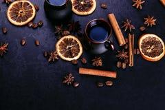 Filiżanka kawy, gwiazdowy anyż, cynamon, wysuszone fasole na ciemnym kuchennym countertop, pomarańczowe i kawowe Fragrant pikantn fotografia royalty free