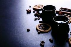 Filiżanka kawy, gwiazdowy anyż, cynamon, wysuszone fasole na ciemnym kuchennym countertop, pomarańczowe i kawowe Fragrant pikantn obraz stock