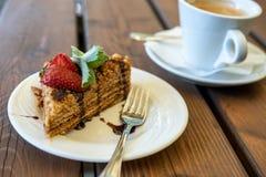 Filiżanka kawy i kawałek miodowy gąbka tort dekorujący z truskawkami i mennicą na drewnianym stole zdjęcia royalty free