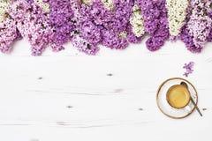 Filiżanka kawy i lili kwiaty graniczymy na białym drewnianym backgroun Fotografia Stock