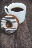 Filiżanka kawy i pączek na drewnianym biurku Zdjęcia Stock