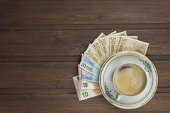 Filiżanka Kawy i pieniądze Ważni banknoty na drewnianym stole Fotografia Stock