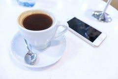 Filiżanka kawy i smartphone na stole w kawiarni, bufet zdjęcie royalty free