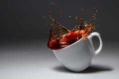 Filiżanka kawy lub herbata spadaliśmy iluminująca powierzchnia Zdjęcia Stock