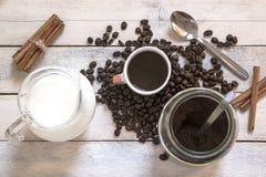 Filiżanka kawy, mleko, cynamon i niektóre kawowe fasole na drewnianym stole w nieociosanej kuchni, pusta kopii przestrzeń zdjęcia stock