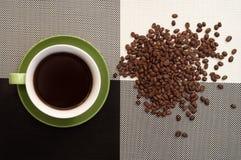 Filiżanka kawy na czarny i biały, rozrzuconych fasolach, Klasyczny surowy styl fotografia royalty free