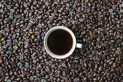 Filiżanka kawy na kawowych fasoli stosie zdjęcia royalty free