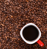 Filiżanka kawy na kawowych fasoli tle Zdjęcia Royalty Free
