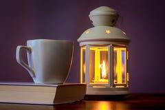 Filiżanka kawy na książce blisko lampionu z świeczką w evening_ zdjęcie royalty free
