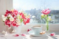 Filiżanka kawy na nadokiennej desce, światło słoneczne po deszczu z obraz royalty free