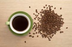 Filiżanka kawy na rozpraszać kawowych fasolach i stole najlepszy widok Obraz Royalty Free