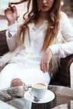 Filiżanka kawy na szklanym stole z dziewczyną w białym kostiumu znowu Obraz Stock