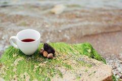 Filiżanka kawy na wody morskiej i kamienia tle Denny świeżość ranku pojęcie obrazy stock