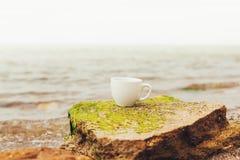 Filiżanka kawy na wody morskiej i kamienia tle Denny świeżość ranku pojęcie zdjęcia stock