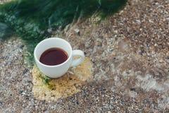 Filiżanka kawy na wody morskiej i kamienia tle Denny świeżość ranku pojęcie obraz royalty free