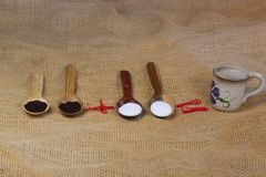 filiżanka kawy obok drewnianych łyżek z kawowego i cukrowego latte tła stołu mleka białym gorącym cappuccino obraz royalty free