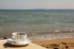 Filiżanka kawy przy plażą Fotografia Stock