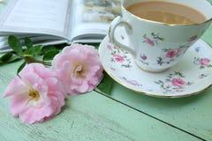 Filiżanka kawy, różowe róże i książki na stary drewnianym, Obraz Stock