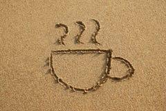 Filiżanka kawy rysuje na piasek plaży na zmierzchu zdjęcia royalty free