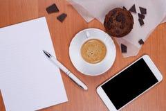 Filiżanka kawy, słodka bułeczka i czekolady kawałki przy pracującym miejscem, fotografia stock