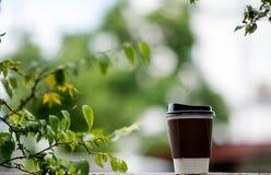 Filiżanka kawy umieszcza w rękach i w podłoga z n zdjęcia royalty free