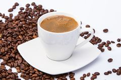 Filiżanka kawy wśród kawowych fasoli Obraz Stock