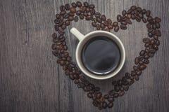 Filiżanka kawy wśrodku kawowych fasoli kierowych Obrazy Stock