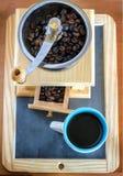 Filiżanka kawy, warząca z fasolami i kawowym ostrzarzem Zdjęcia Royalty Free