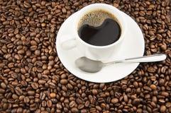 Filiżanka kawy z łyżką na kawowych fasolach Fotografia Royalty Free