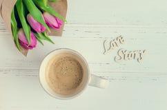 Filiżanka kawy z bukietem różowi tulipany LOVE STORY i drewniani słowa Fotografia Stock