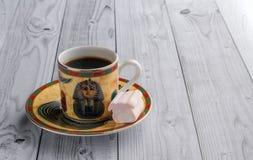 Filiżanka kawy z egipcjanów wzorami i słodkimi marshmallows na lekkim drewnianym tle fotografia stock