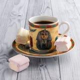Filiżanka kawy z egipcjanów wzorami i słodkimi marshmallows na lekkim drewnianym tle obrazy stock