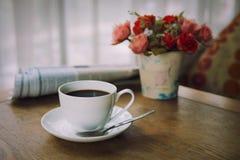 Filiżanka kawy z gazetą na stole w ranku, grże brzmienie fotografia royalty free