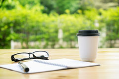 Filiżanka kawy z glassess i notepad na drewnianym stole nad zielenią Fotografia Royalty Free