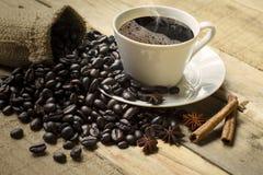 Filiżanka kawy z kawowymi fasolami i pikantność obrazy stock