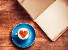 Filiżanka kawy z kierową pobliską książką obrazy royalty free