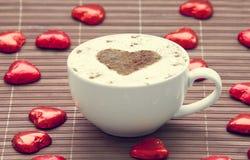 Filiżanka kawy z kierowym symbolem wokoło i cukierkiem. Obraz Stock